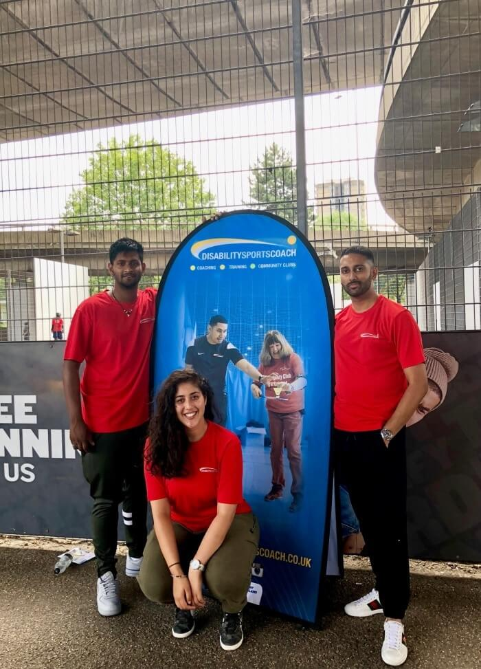 Men and woman posing in front of a rollup banner