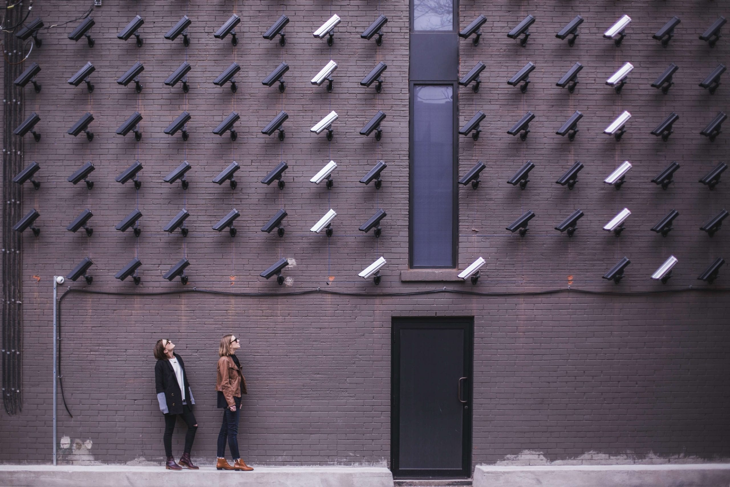 Two women outside building with security cameras art installation