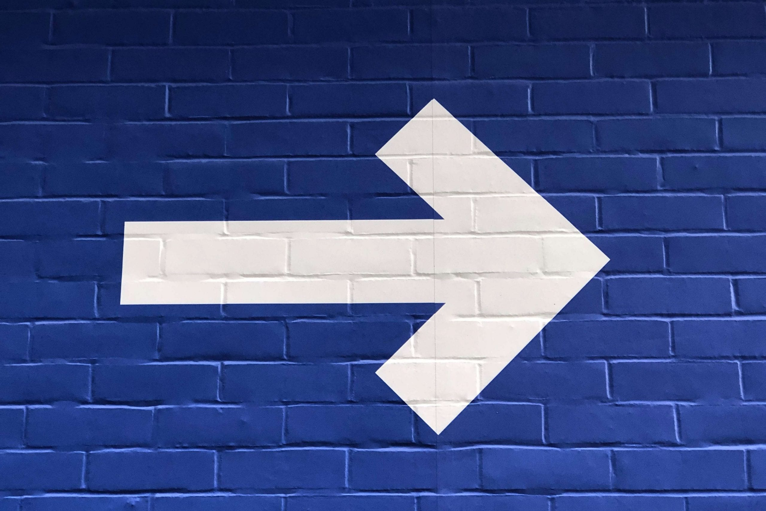 White-arrow-on-a-blue-wall