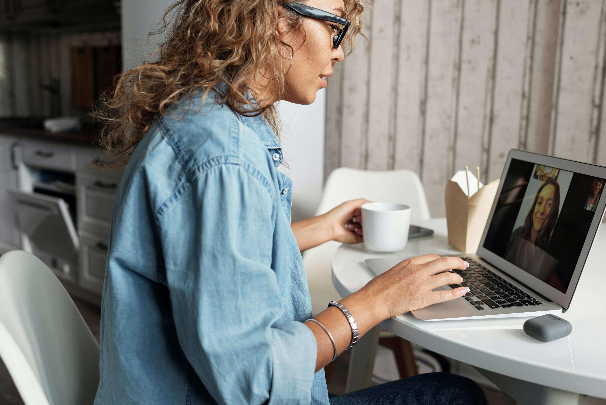Woman in Blue Denim Jacket Using Macbook Pro