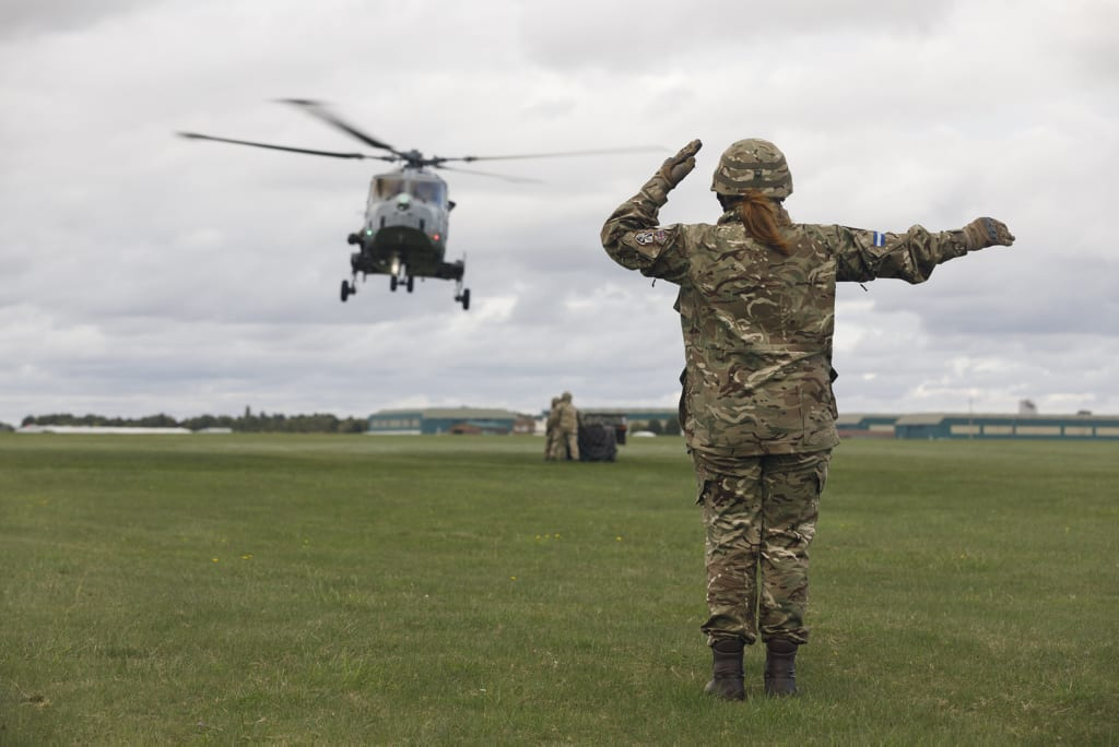 Female Air Trooper signalling helicopter