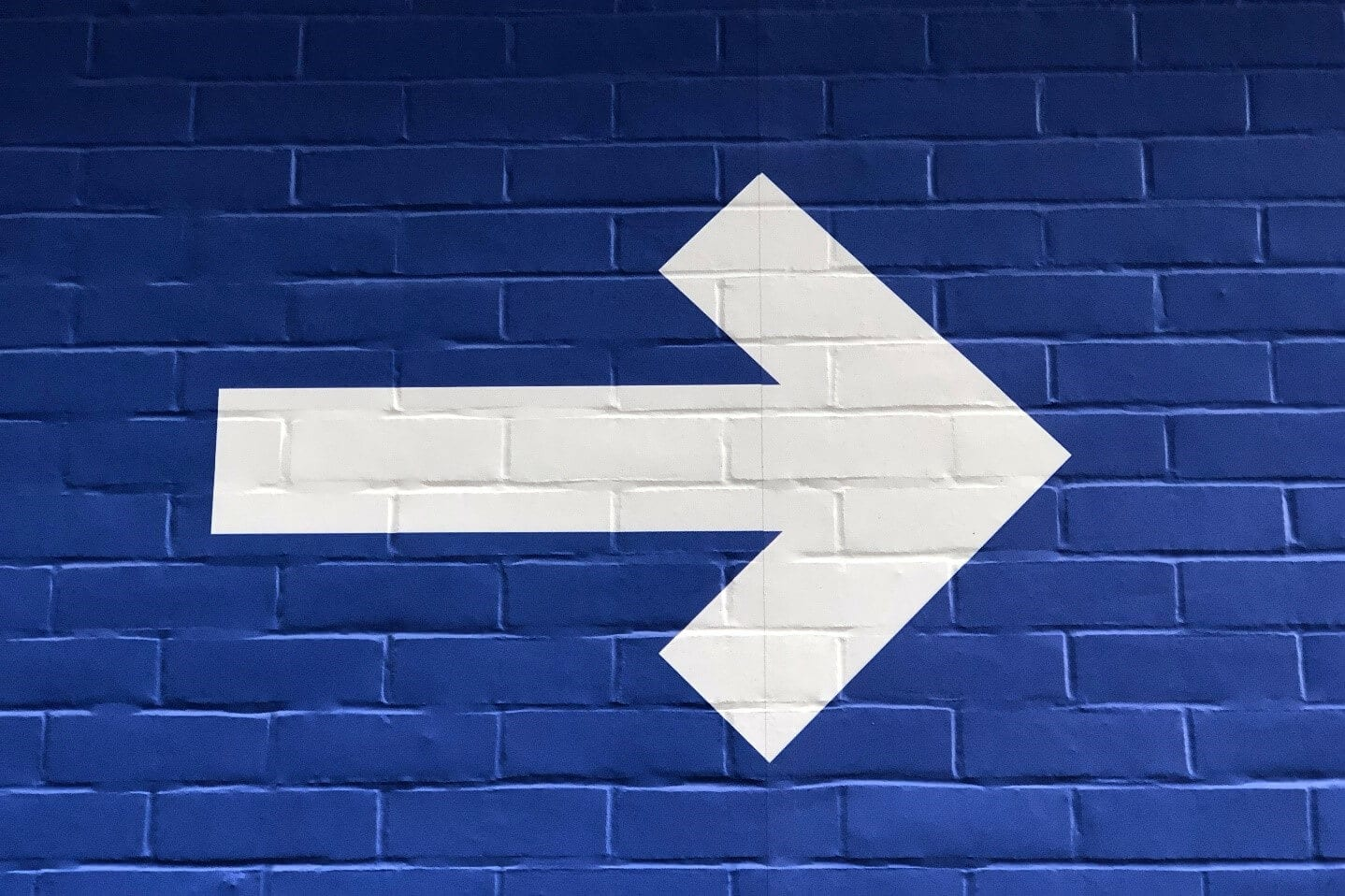 White painted arrow on a blue brick background