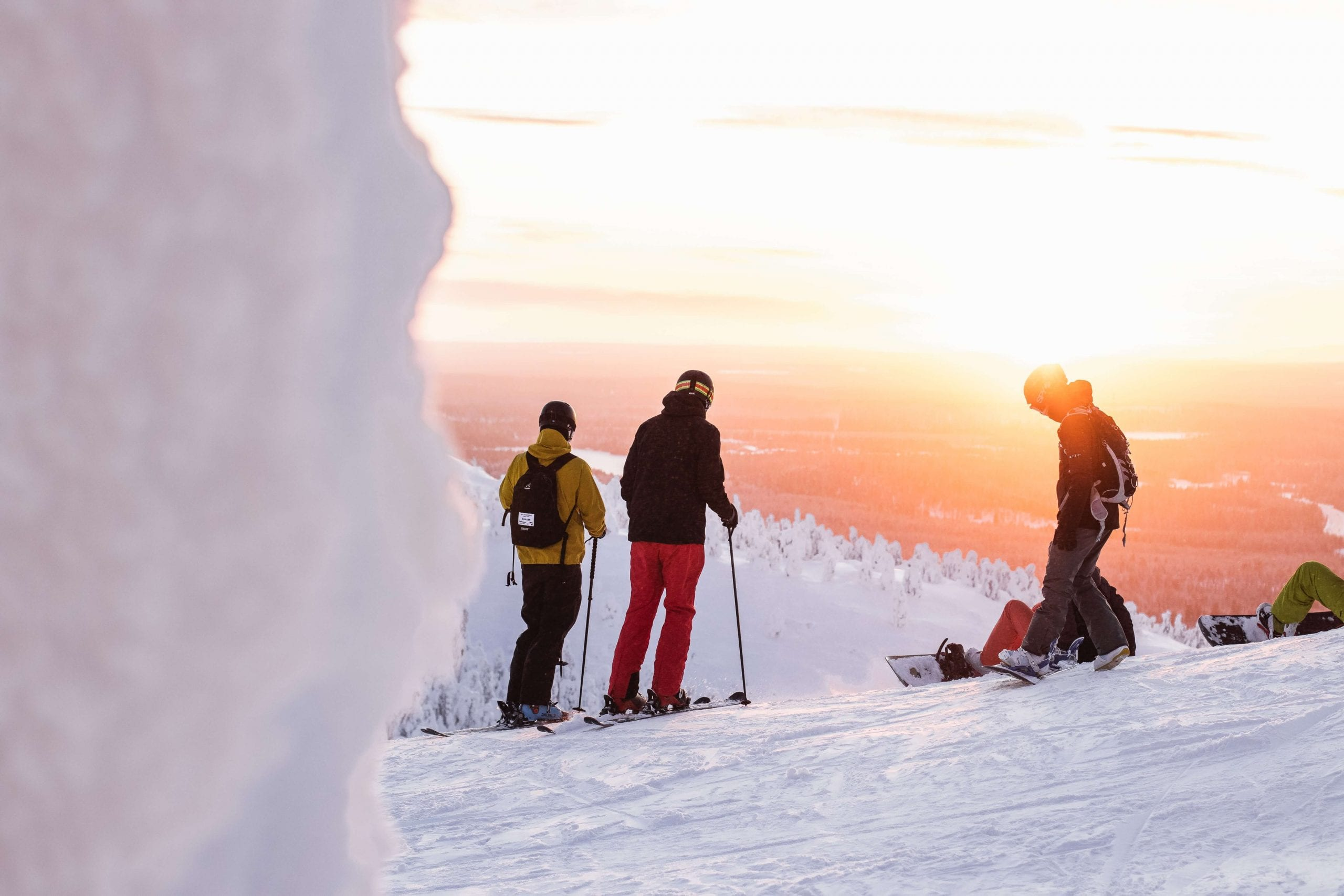 Skiers at the top of a mountain at sunset