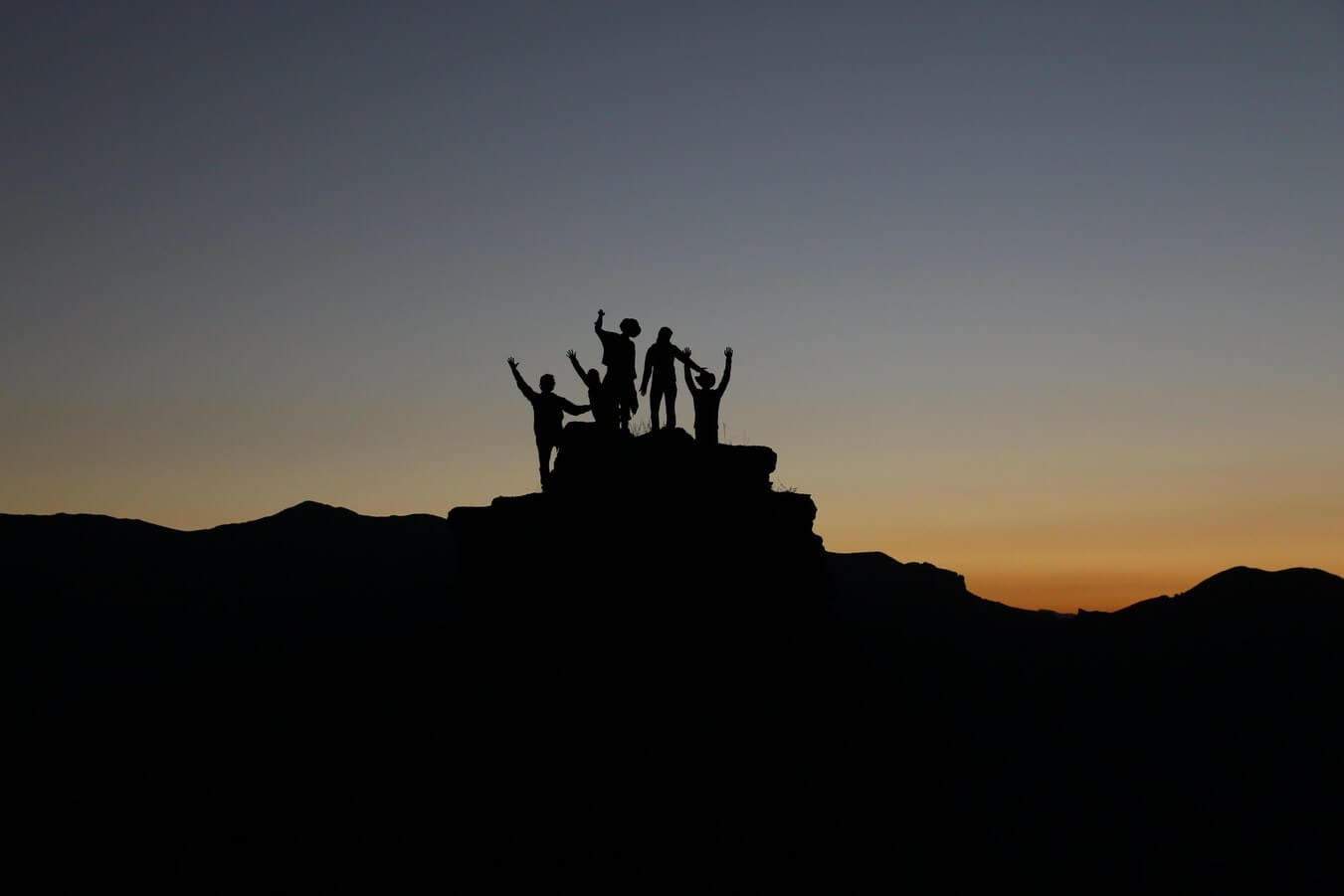 People on top of a mountain with a sunset