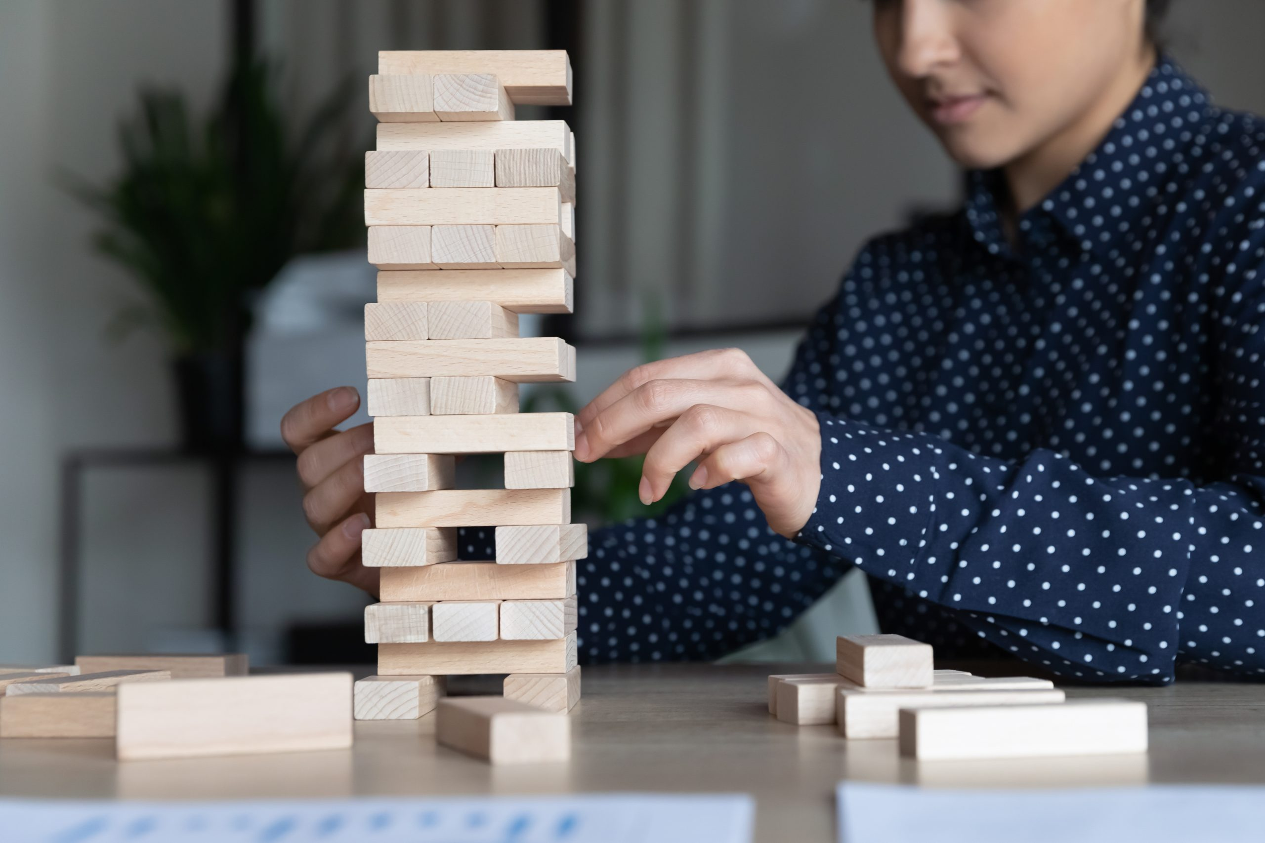 Indian businesswoman sitting at workplace desk build tower of wooden blocks play game, apply skills and creative approach close up image. Improve precision, business strategic thinking concept