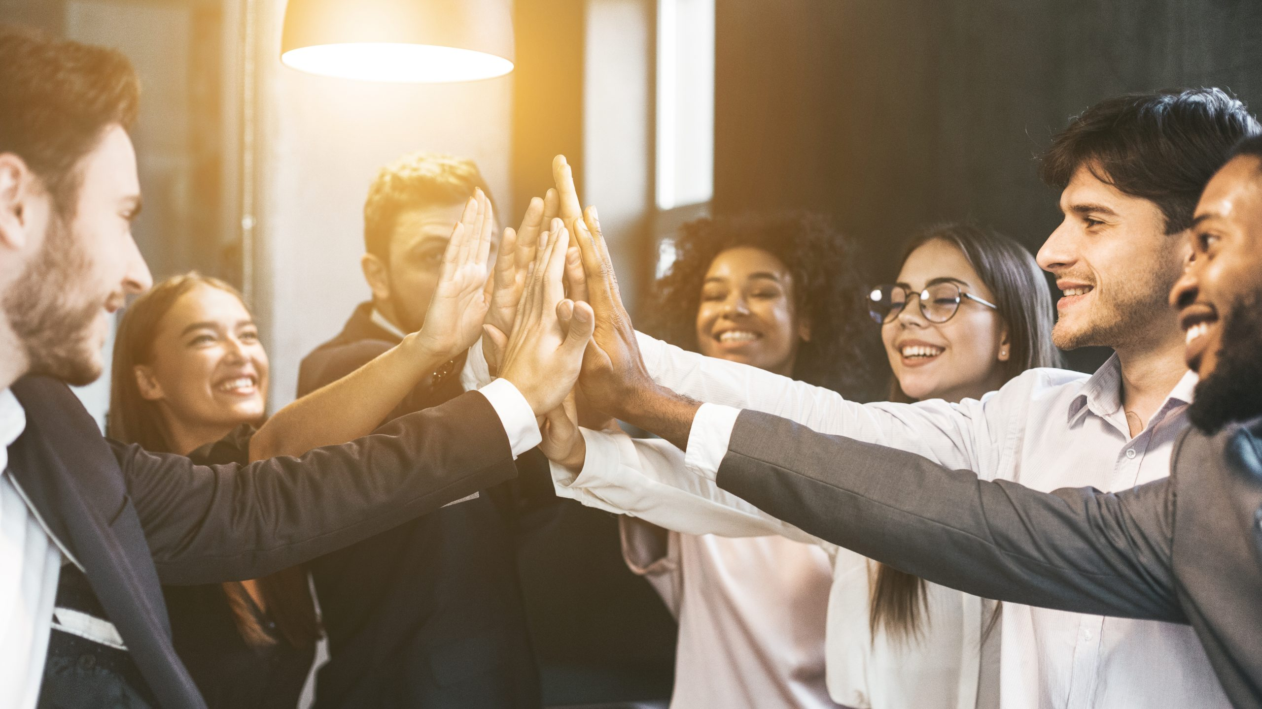 group of employees doing a high-five for success