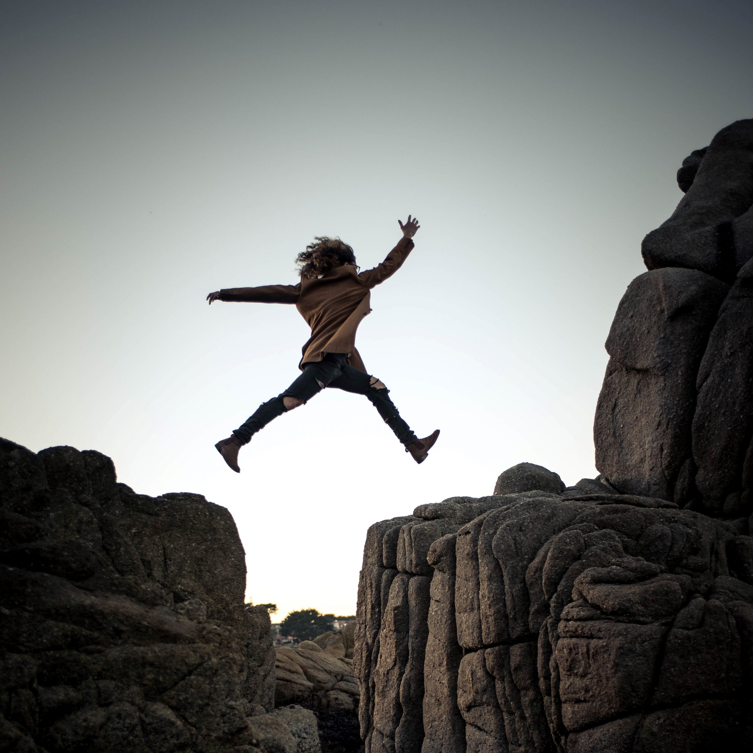girl jumping across a cliff ridge